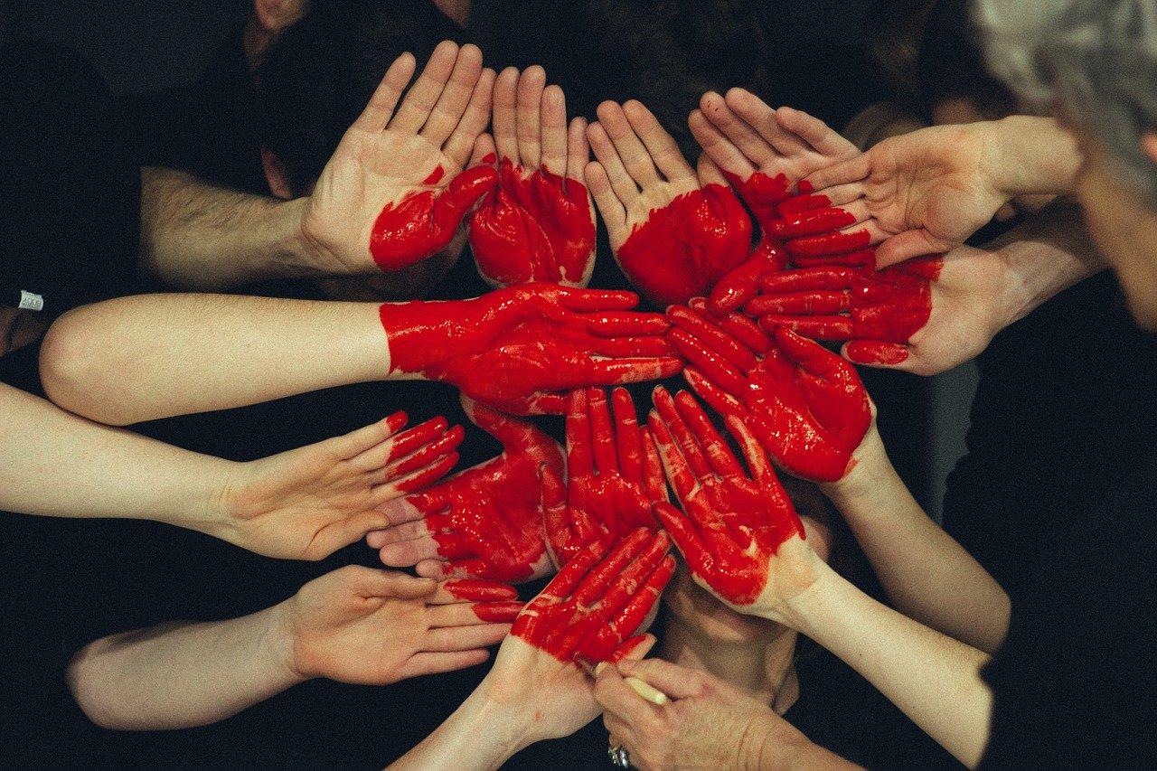Mehrere Hände die zusammen mit der Farbe auf den Händen ein Herz bilden