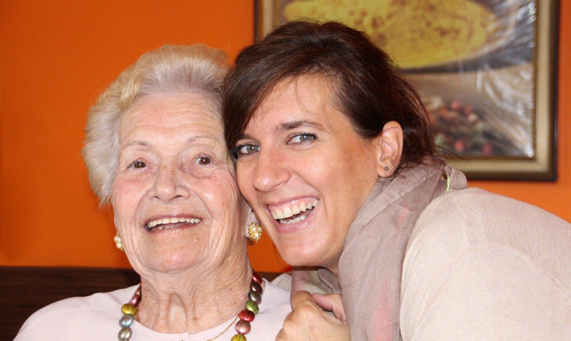 Junge Frau liegt in arm einer alten Frau und lachen glücklich