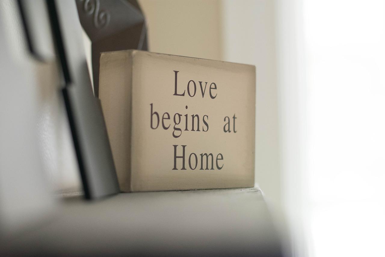 """Schild mit Aufschrift """"Love begins at Home"""""""